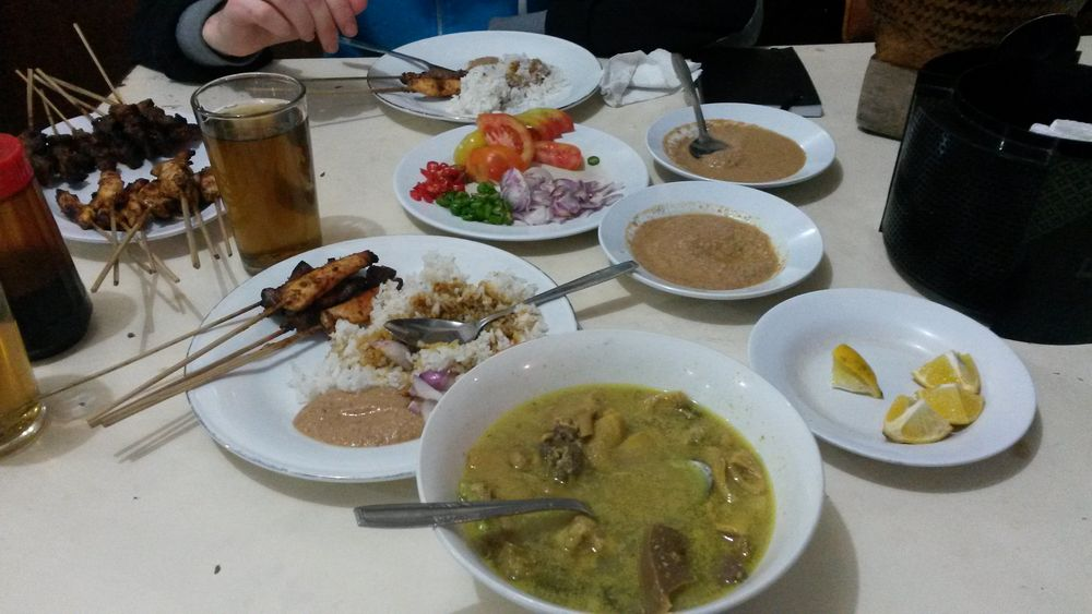 Soto kambing - kozí polévka s kokosovým mlékem, v pozadí sate z kuřecího a kozího masa