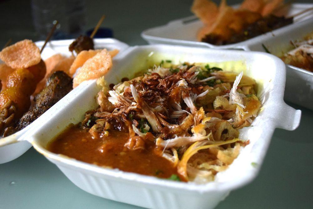 Bubur ayam - rýžová kaše s kuřetem, omáčkou a saté z vajíček a jatýrek