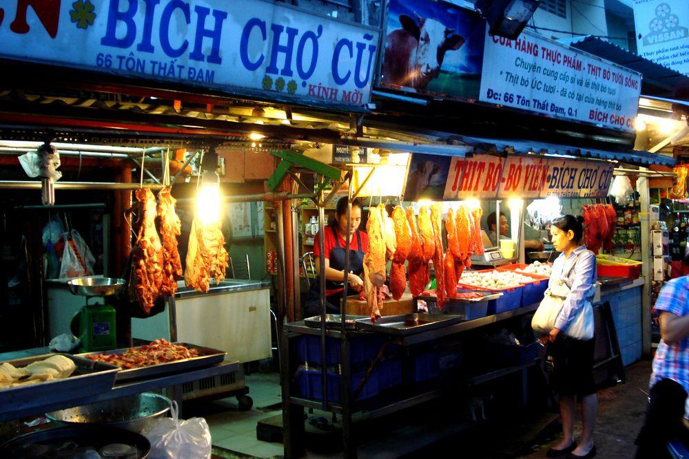 Noční vietnamská tržnice s masem a zeleninou v Ho Chi Minh City